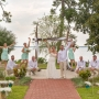 A fun wedding photos with the bride and groom with their arms raised, the bride's maids jumping in the air and groom's men crouching down with the backdrop of Wolf Bay at the Coastal Arts Center of Orange Beach