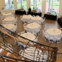 A wedding setup in the open gallery at the Coastal Arts Center of Orange Beach with round tables and white tablecloths