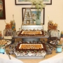 A decorative cake and dessert table set up at the Coastal Arts Center of Orange Beach