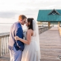 A bride and groom have an intimate moment leaning into each other, before or after a kiss, on the Waterfront Park Pier next to the Coastal Arts Center of Orange Beach