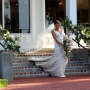 A bride walks down the back porch steps holding a stunning bouquet with her long white veil trailing behind her at the Coastal Arts Center of Orange Beach