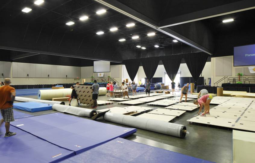 Inside the Orange Beach Event Center being set up for a gymnastics competition with pads in different configuration