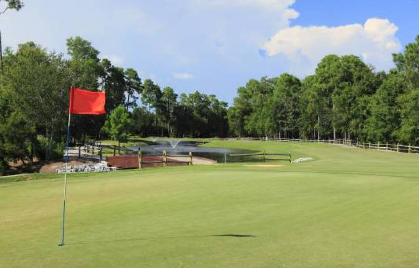 A golf hole flag on green at Orange Beach Golf Center