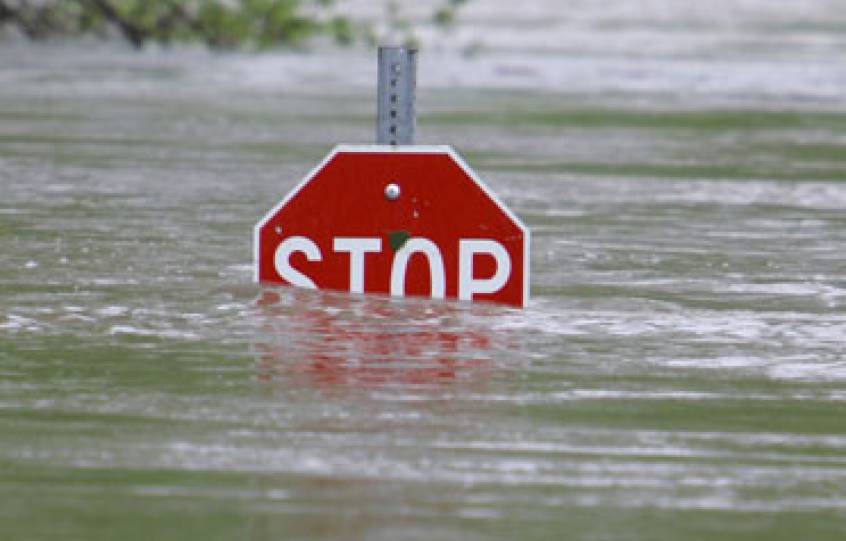 A stop sign is nearly submerged in flood waters with the water line up to the letters of the sign