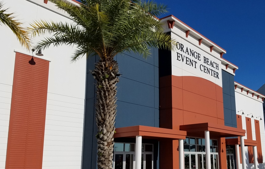 Front facade of the Orange Beach Event Center with palm trees