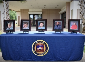 Five photos in frames shows four Orange Beach PD sworn officers and one non-sworn officer who were remembered during the Orange Beach Police Department's Remember the Fallen observance on Friday, May 10, 2019